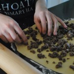 Charis of S. A. T. gourmet photo of her placing butter and bittersweet chocolate crumbles on the rolled out dough
