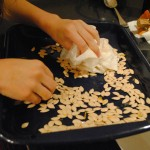 Photo of Charis blotting the water off of pumpkin seeds for a blog post on baked pumpkin seeds on S.A.T.gourmet.