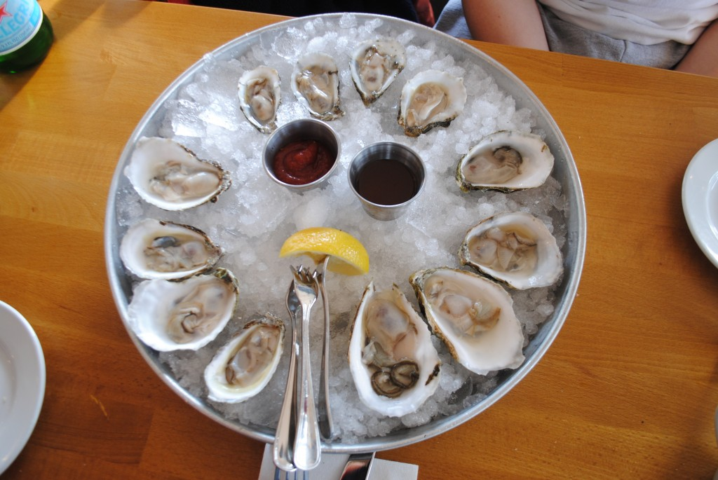 Photo of twelve oysters on a plate with lemon, horseradish sauce and cocktail sauce, an appetizer offered at Matunuck Oyster Bar, for a restaurant review by Charis Freiman-Mendel, author of Cook Your Way THrough The S.A.T.