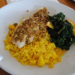 Photo of pistachio crusted atlantic cod loin with curry brown butter, saffron rice and braised kale at Matunuck Oyster Bar, for a restaurant review by Charis Freiman-Mendel, author of Cook Your Way THrough The S.A.T.