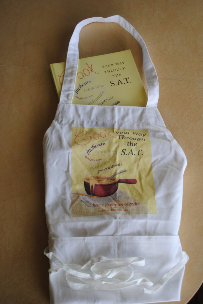 "Photo of ""Cook Your Way THrough The S.A.T."" book and apron, prizes for contest sponsored by Charis Freiman-Mendel of S.A.T. gourmet and SLJ-Teen"