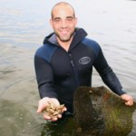 Photo of Matunuck Oyster Bar owner Perry Raso holding oysters in his palm while wading in Potter Pond, for a restaurant review by Charis Freiman-Mendel, author of Cook Your Way THrough The S.A.T.